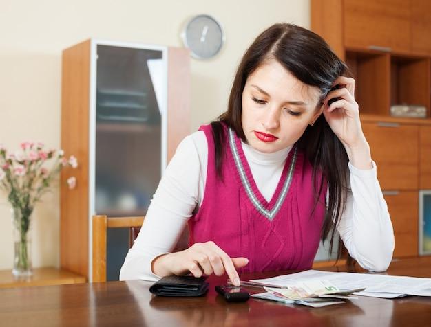 Ernste hausfrau, die rechnungen der dienstprogrammzahlungen ausfüllt