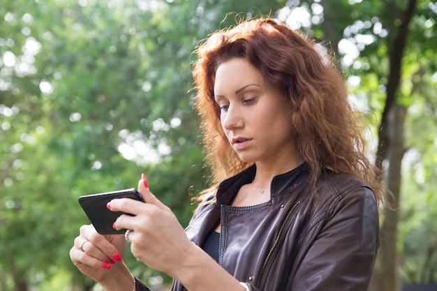 Ernste hübsche dame, die auf smartphone im stadtpark grast