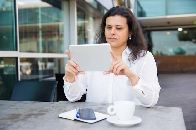 Ernste hübsche damenlesennachrichten auf tablette im straßencafé