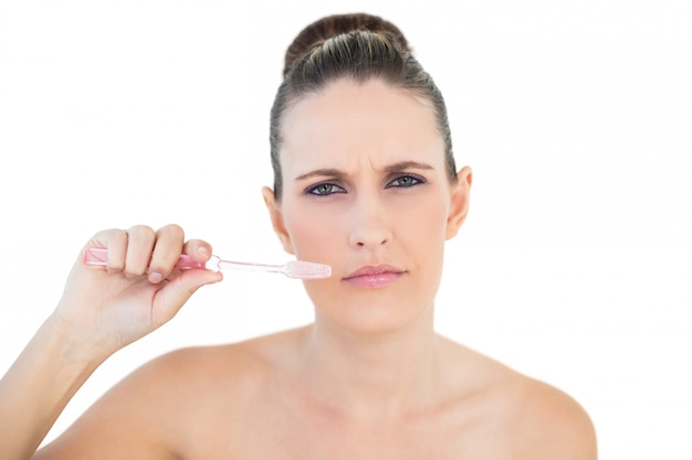 Ernste hübsche frau, die ihre zähne putzt