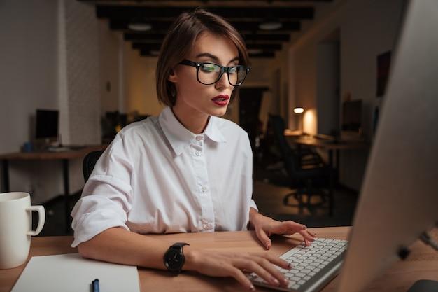 Ernste hübsche junge geschäftsfrau mit brille, die computer im büro arbeitet und benutzt