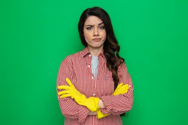 Ernste hübsche kaukasische putzfrau mit gummihandschuhen, die mit verschränkten armen steht und schaut