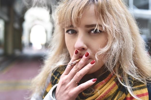 Ernste junge blonde frau auf grauem hintergrund raucht, die kamera anschaut