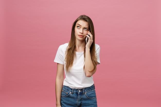 Ernste junge frau, die am telefon lokalisiert auf rosa spricht.