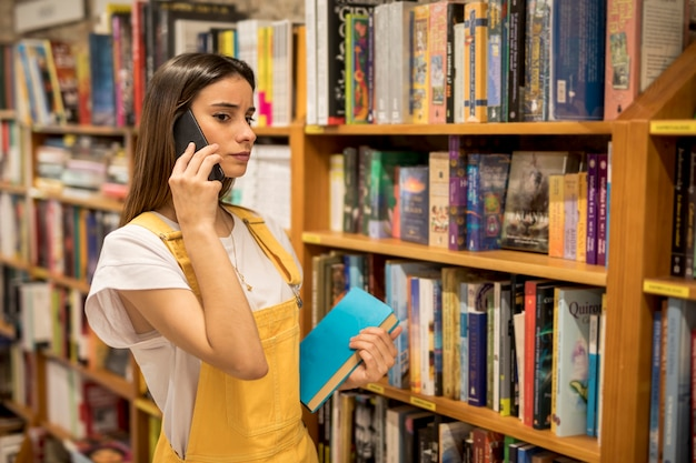 Ernste junge frau, die am telefon nahe bücherregalen spricht