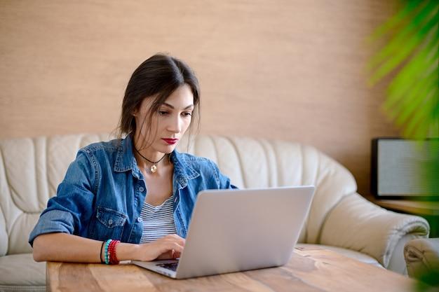 Ernste junge frau, die an einem laptop im büro arbeitet