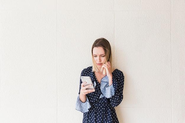 Ernste junge frau, die mobiltelefon hält