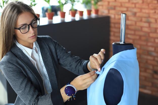 Ernste junge frau in brillen, die nähnadeln zum nähen einer jacke auf einer schaufensterpuppe verwendet, während sie in ihrer werkstatt steht.