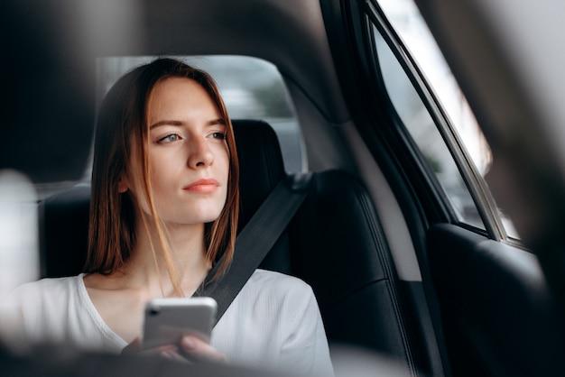 Ernste junge frau mit einem smartphone, der im auto sitzt und heraus schaut