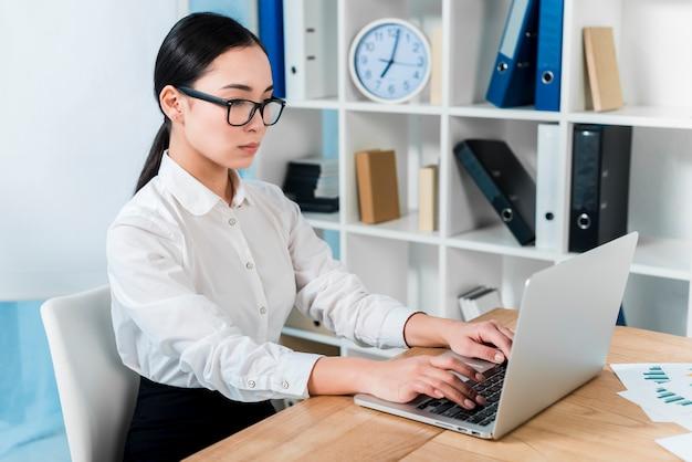 Ernste junge geschäftsfrau, die auf laptop über dem schreibtisch schreibt