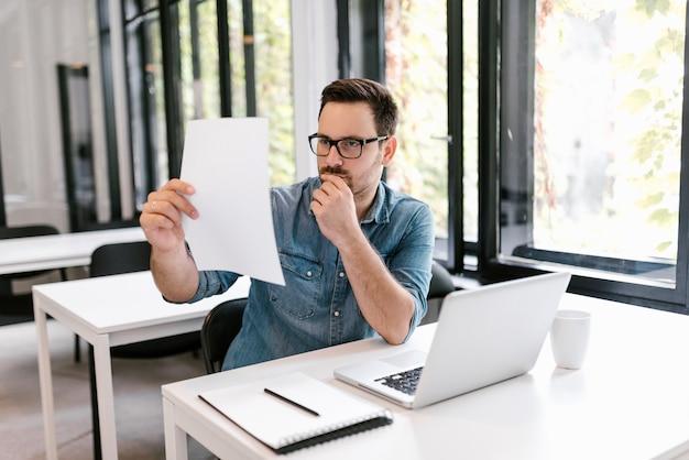 Ernste junge geschäftsmannleseschreibarbeit am schreibtisch im büro.