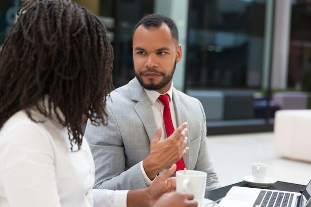 Ernste junge kollegen, die arbeitsfragen besprechen