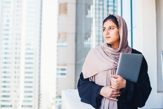 Ernste junge muslimische frau im hijab, die einen laptop im freien hält