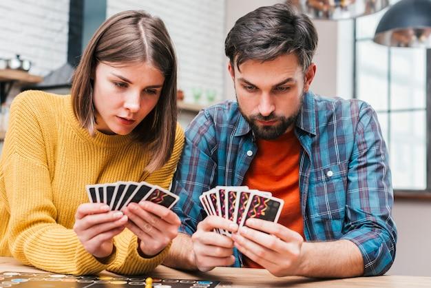 Ernste junge paare, welche die karten spielen das brettspiel betrachten