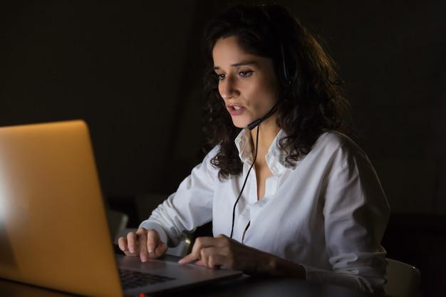 Ernste kundenkontaktcenterarbeitskraft mit kopfhörer und laptop
