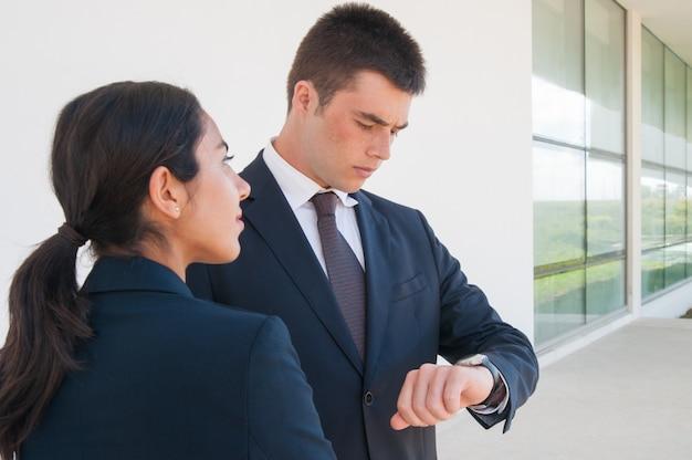 Ernste mitarbeiter, die geschäftspartner warten