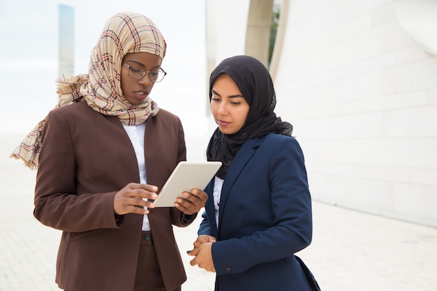 Ernste moslemische geschäftsfrau, die projektdetail erklärt