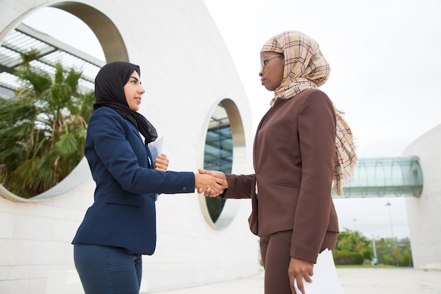 Ernste moslemische geschäftsfrauen, die sich grüßen