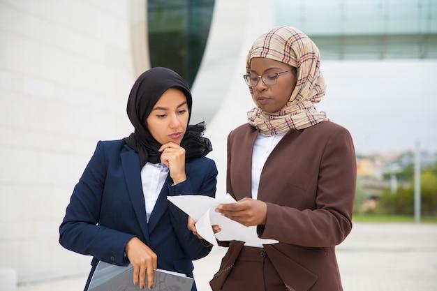 Ernste moslemische geschäftskollegen, die draußen dokumente wiederholen