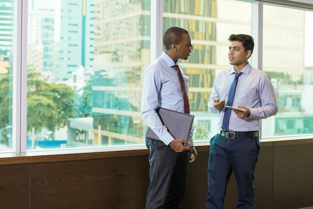 Ernste multiethnische rechtsanwälte, die am großen bürofenster sprechen