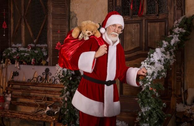 Ernste, nachdenkliche santa claus, die eine tasche mit geschenken hält.