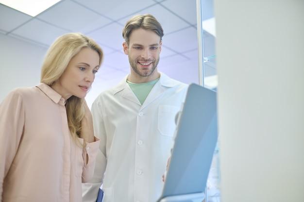 Ernste patientin und ein fröhlicher männlicher arzt, der etwas hinterfragt