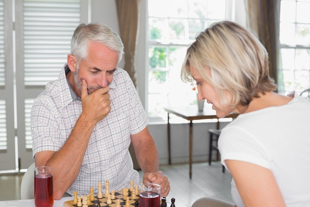 Ernste reife paare, die zu hause schach spielen