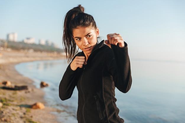 Ernste sportfrau, die fitnessübung macht und sich auf den kampf vorbereitet