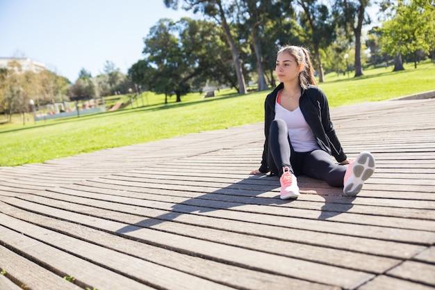 Ernste sportliche dame, die sich draußen entspannt