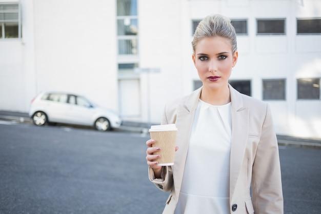 Ernste stilvolle geschäftsfrau, die kaffee hält