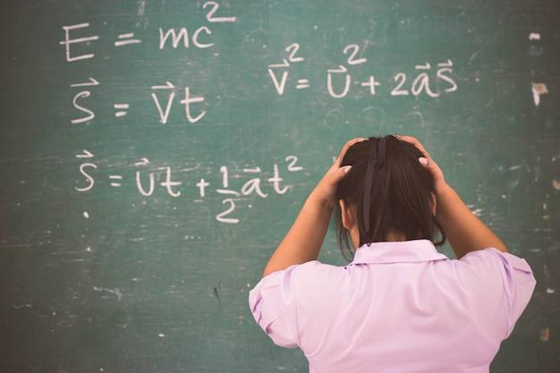 Ernste studentin über physikformel im klassenzimmer.