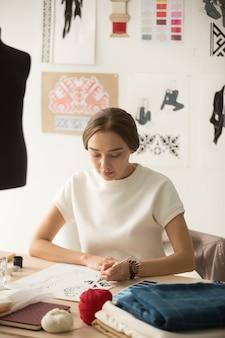 Ernste tausendjährige schneiderin zeichnet neue kapselkollektion