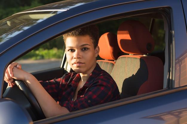 Ernste und schöne afroamerikanerin mit kurzen haaren in einem auto, lebensstil.