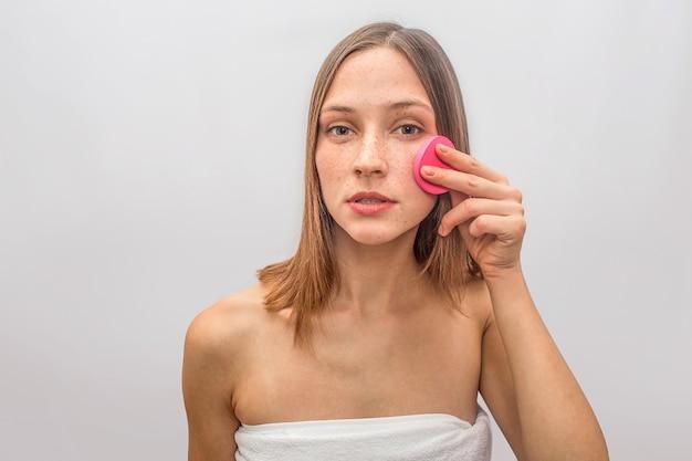 Ernste und starke junge frau schaut und tut hautpflegeprozeduren. sie benutzt dafür einen rosa schwamm. schönes modell sieht zuversichtlich aus.