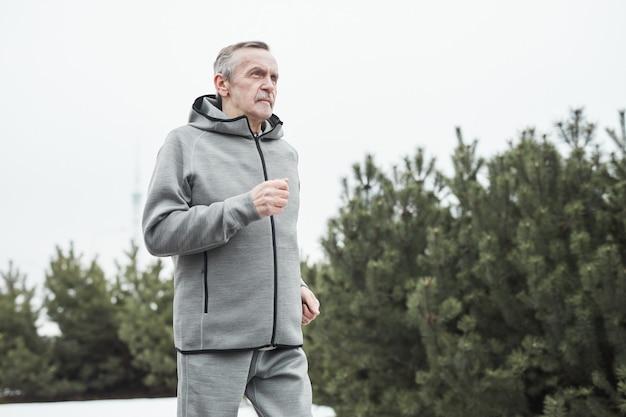 Ernster älterer kaukasischer mann in grauem sportanzug, der die arme schwingt, während er allein im wald läuft
