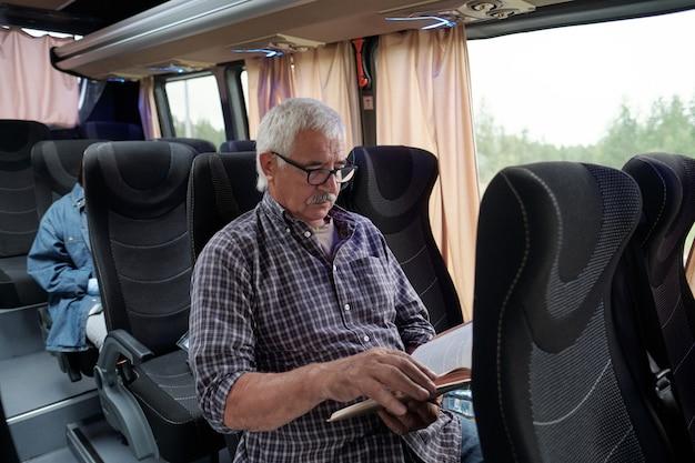 Ernster älterer männlicher passagier mit brille, der auf einem stuhl in einem modernen bus sitzt und ein buch liest