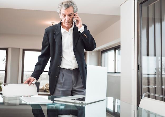 Ernster älterer mann, der am handy mit laptop und digitaler tablette auf reflektierendem schreibtisch spricht