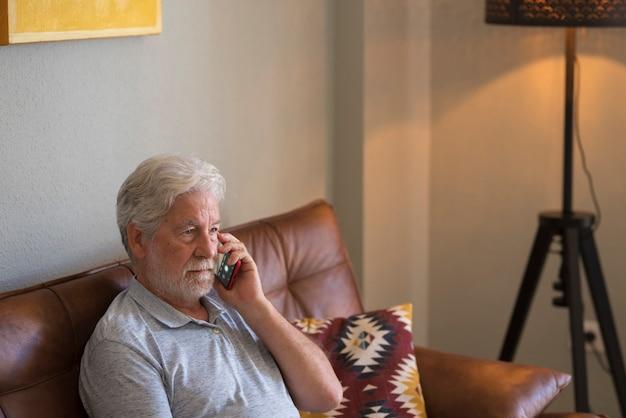Ernster älterer mann, der zu hause mit smartphone telefoniert - traurige emotionen ältere menschen einsam drinnen - kaukasischer alter mann benutzt modernes gerät, das auf dem sofa sitzt