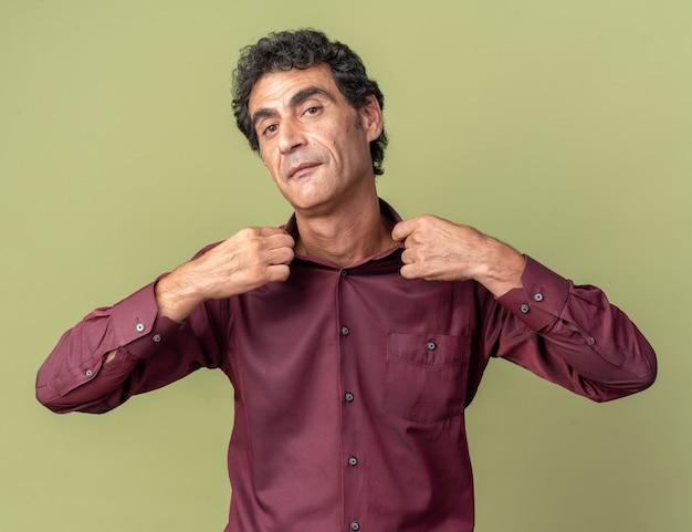 Ernster älterer mann in lila hemd, der mit selbstbewusstem ausdruck in die kamera schaut, der seinen kragen fixiert