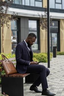 Ernster afrikanischer geschäftsmann im anzug, der im smartphone scrollt