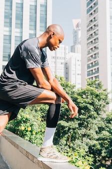 Ernster afrikanischer junger athletenmann, der auf der dachspitze unten schaut steht