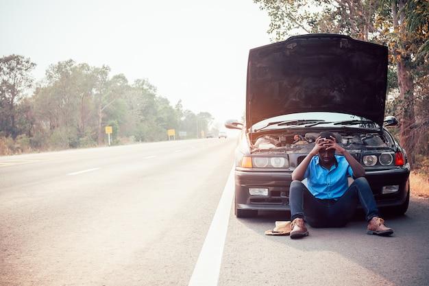 Ernster afrikanischer mann, der seinen kopf durch die hände stehen nahe seinem alten gebrochenen auto hält