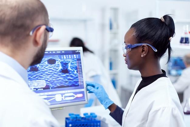 Ernster afrikanischer wissenschaftler, der mit hilfe eines kollegen computer für medizinische experimente verwendet. multiethnisches team medizinischer forscher, die im sterilen labor mit schutzbrille zusammenarbeiten