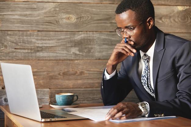 Ernster afroamerikanischer geschäftsmann, der laptop-bildschirm betrachtet und denkt