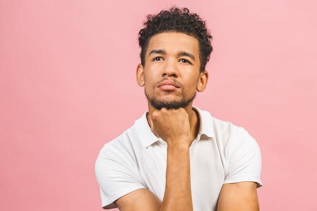 Ernster afroamerikanischer mann, der lokal über rosa hintergrund denkt.