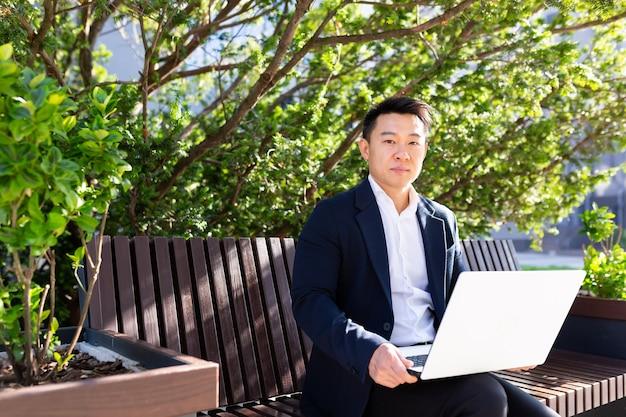 Ernster asiatischer freiberufler im business-anzug, der am laptop arbeitet, der tagsüber auf der bank sitzt und in die kamera schaut