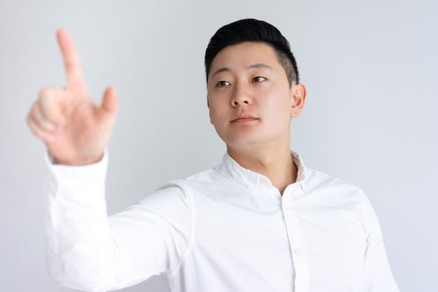 Ernster asiatischer kerl, der unsichtbare wand berührt