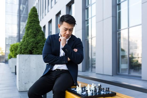 Ernster asiatischer mann, der draußen schach spielt, geschäftsmann denkt, schach zu spielen, der auf einer bank in der nähe des bürozentrums sitzt