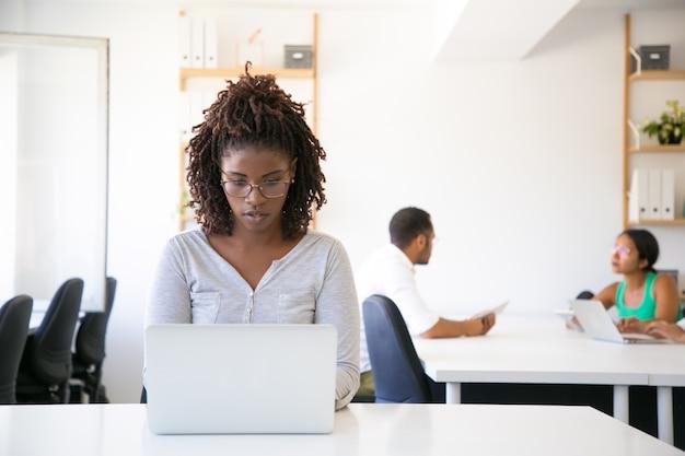 Ernster aufgeregter afroamerikanerangestellter, der an computer arbeitet