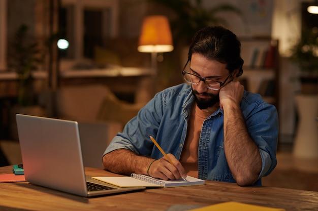 Ernster bärtiger geschäftsmann, der notizen im notizblock macht, der an seinem arbeitsplatz vor laptop sitzt